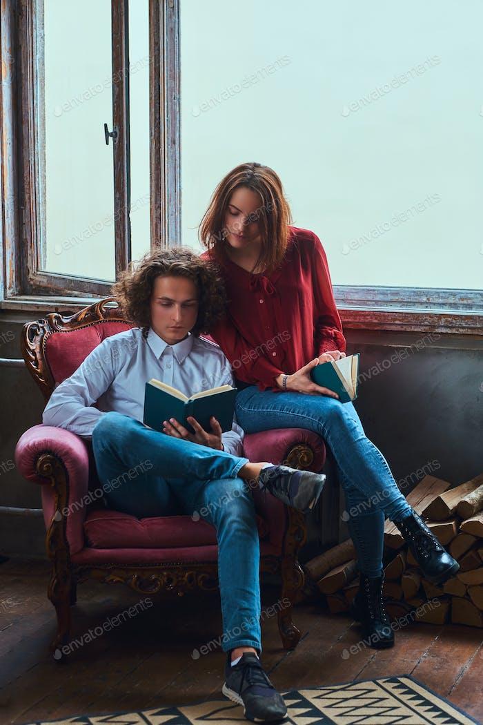 Молодые студенты вместе читают и сидят на стуле.