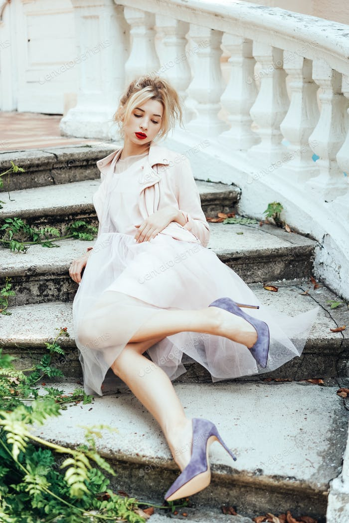 Girl is posing on the stone steps