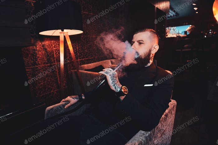 Pensive tattooed man is relaxing on the armchair and is smoking hookah, making hazy vapour