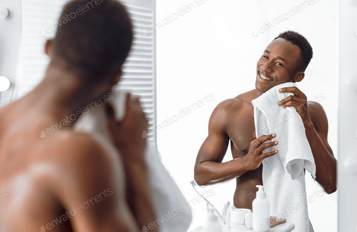 Handsome African American Man Wiping Face With Towel In Bathroom