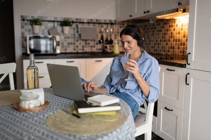 Frau trinkt Wein und mit Laptop in der Küche