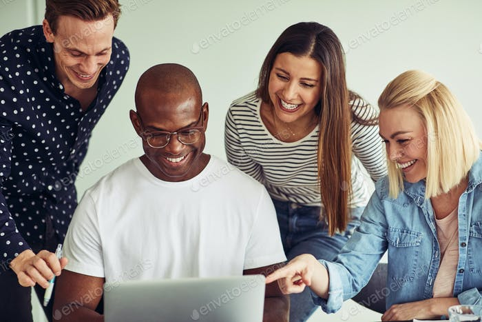 Smiling group of diverse businesspeople working on a laptop together