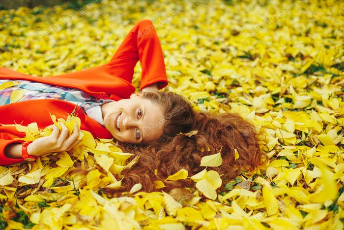 Junge schöne Dame umgeben Herbstblätter