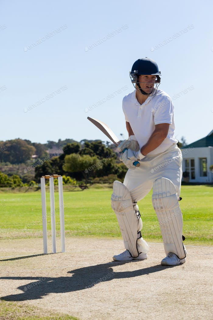 Cricket player batting on pitch against clear sky