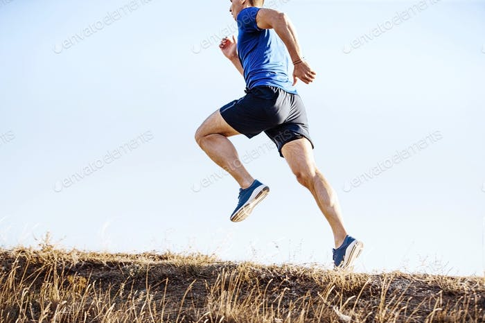 male runner running on mountain trail