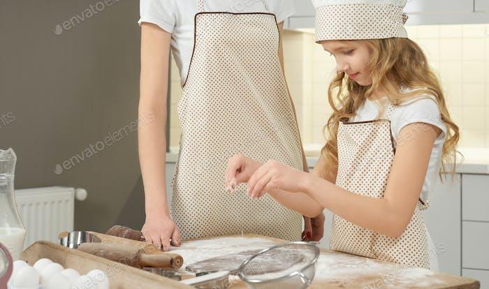 Nettes Mädchen in Schürze Streuen Mehl auf Schokoladenteig