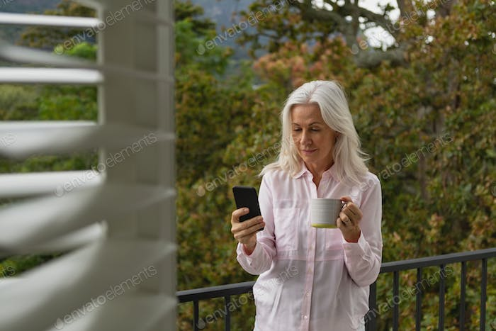 Active senior Caucasian woman using mobile phone while holding coffee mug on the balcony at home