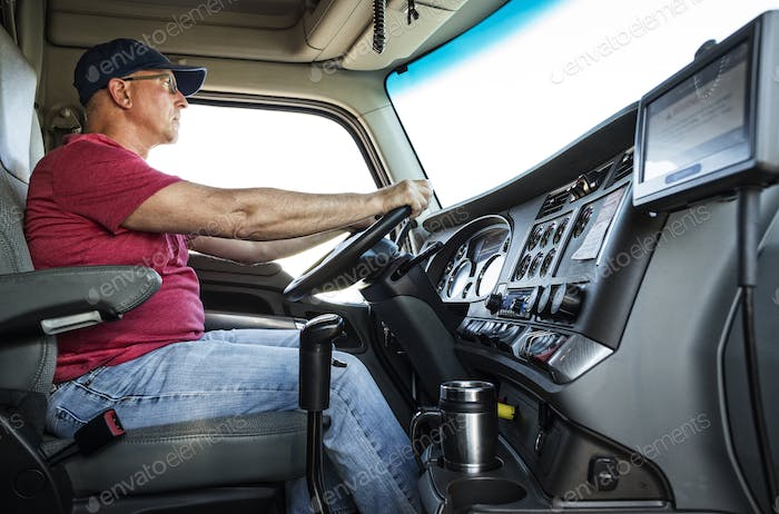 Caucasian man truck driver in the cab of his commercial truck.