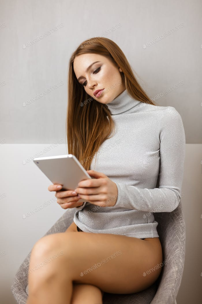 Portrait of young thoughtful lady in sweater sitting on chair and using tablet computer