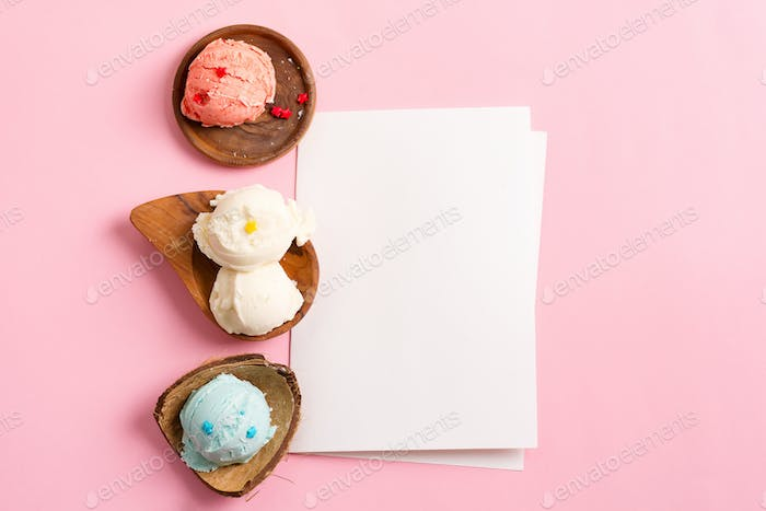 wooden plates with fresh natural colorful ice-cream with paper sheet on a pastel pink background