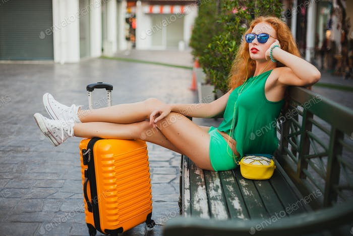 woman traveler with orange suitcase, traveling around world