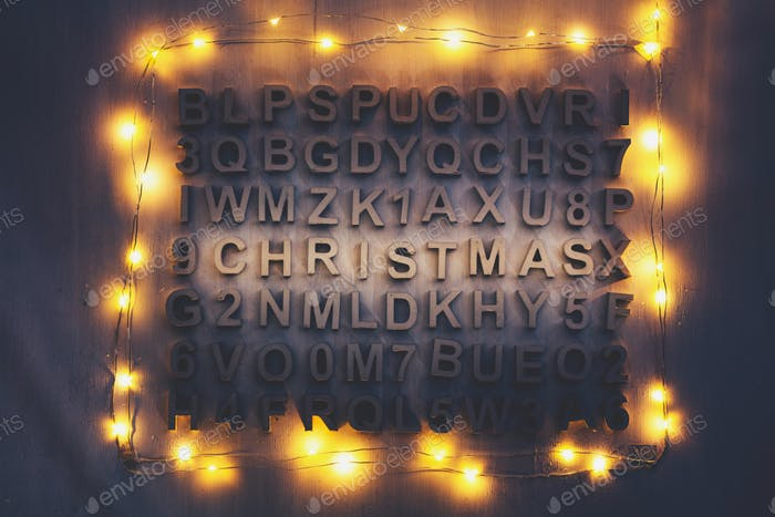 Christmas word made of wooden letters among other random letters.
