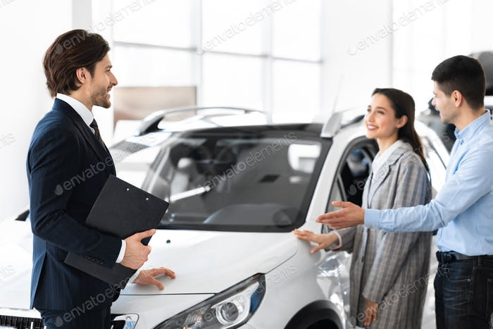 Dealer Showing Young Couple New Auto In Dealership Store