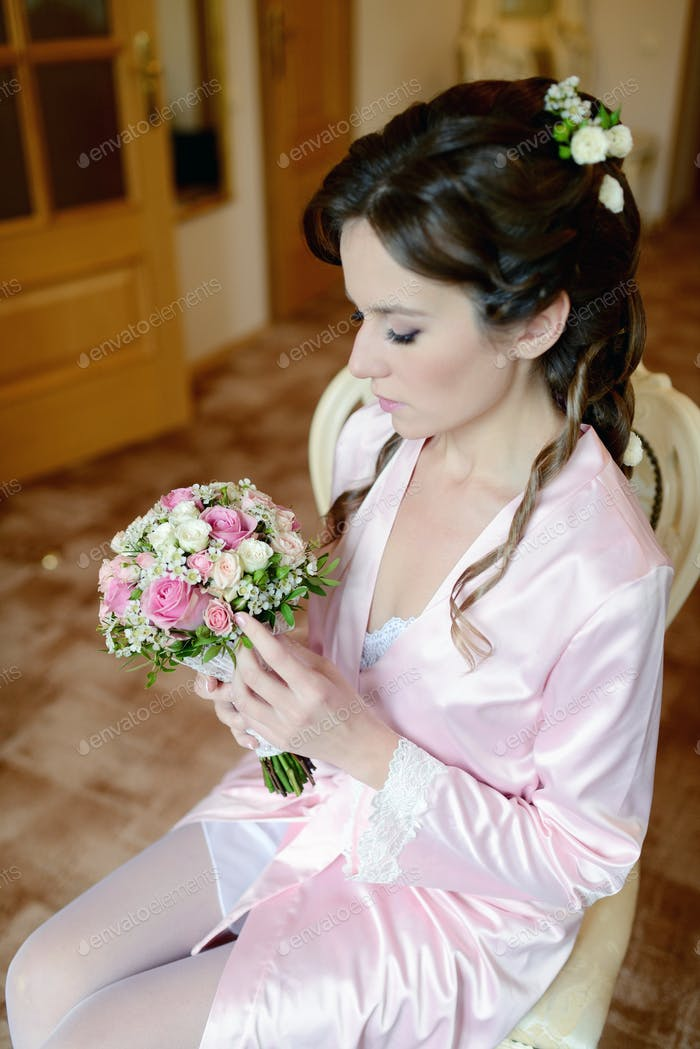 Beauty bride in dressing gown with bouquet and lace veil indoors