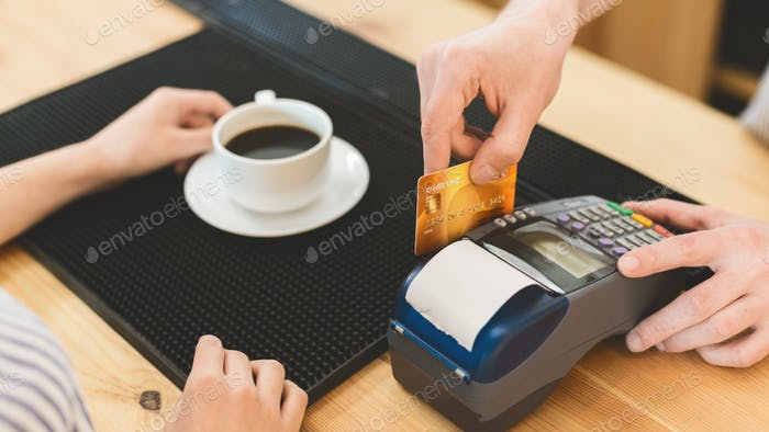 Close up of transaction with credit card in cafe for coffee