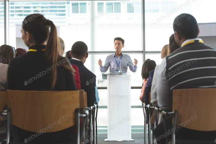 Junge männliche Geschäftsmann spricht vor Business-Profis in Business-Seminar im Büro
