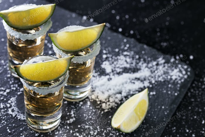Black background with tequila glasses scattered with salt and lime