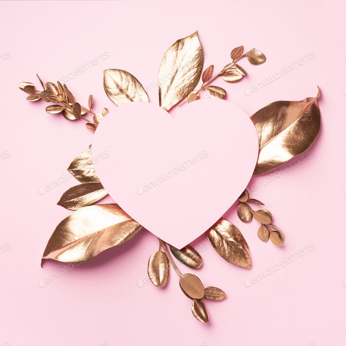 Golden leaves, heart shaped paper on pink background with copy space. Top view. Copy space. Summer