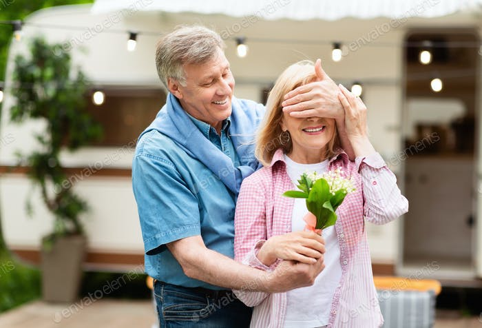 Holiday celebration. Cheerful mature man surprising his wife with bouquet of flowers on campground