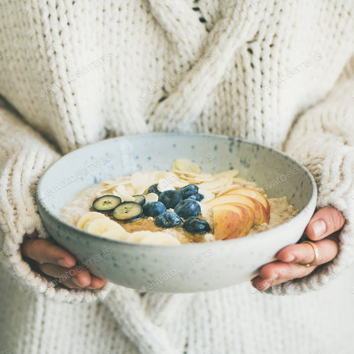 Woman in sweater holding bowl of oatmeal porriage, square crop
