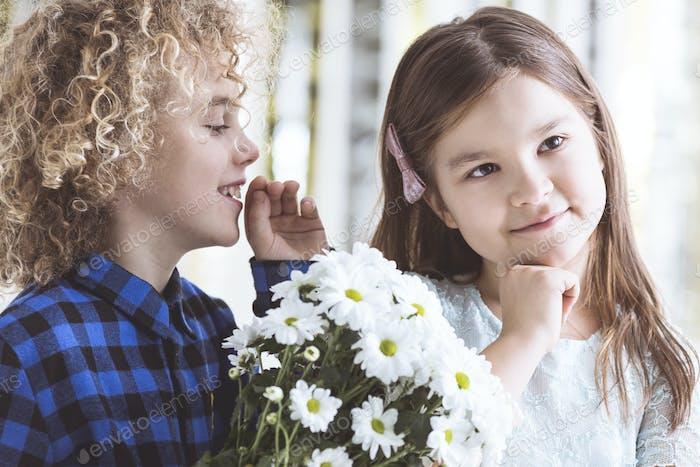Junge flüsterte ins Ohr des Mädchens
