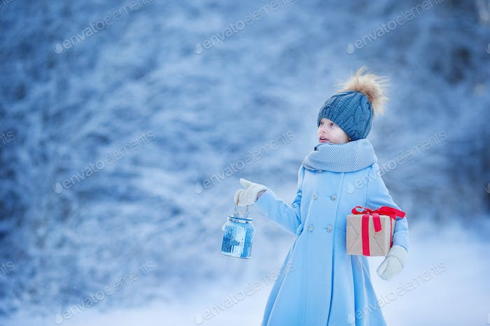 Adorable girl with lamp and christmas box gift in winter on Xmas eve outdoors