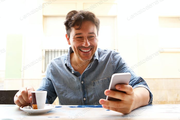 cheerful older man with smart phone and cup of coffee