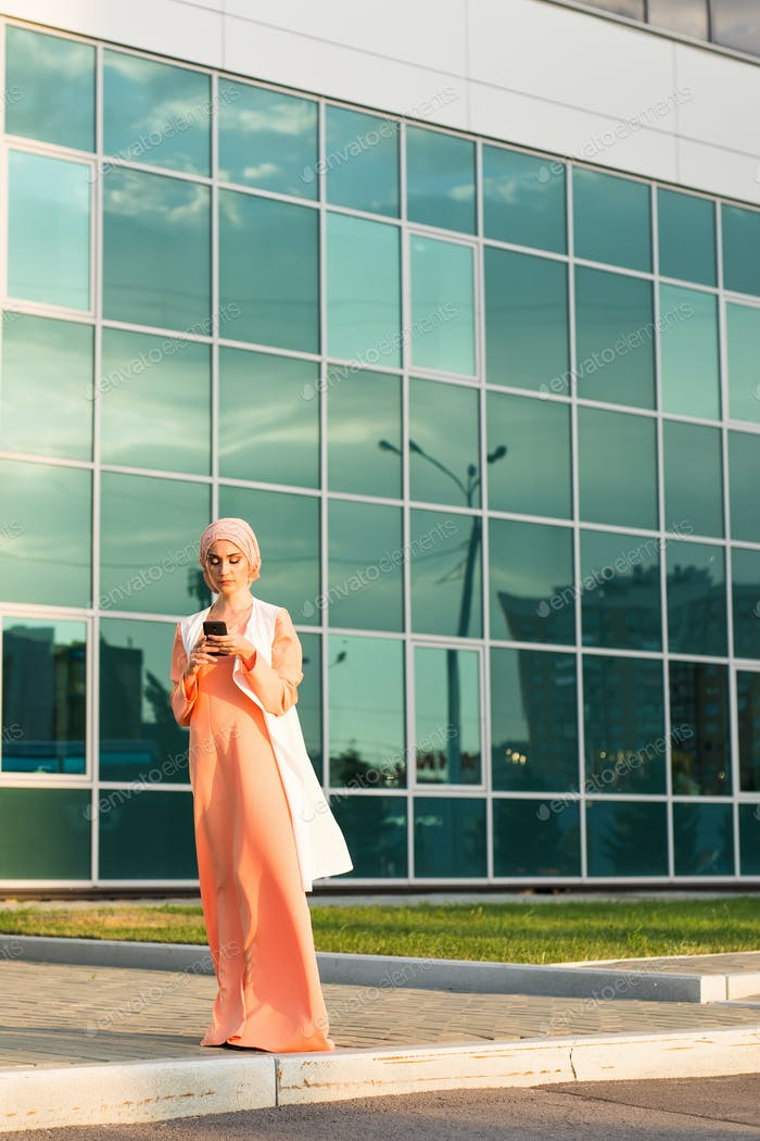 Portrait of Muslim woman wearing Hijab outdoor using mobile phone