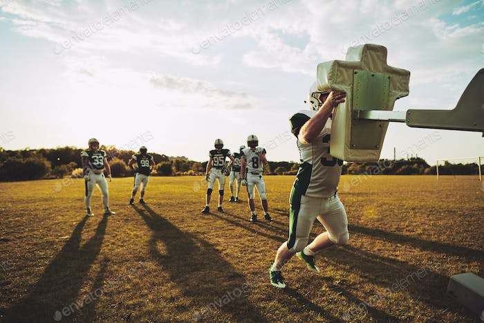 Football players doing tackling drills together on a sports field