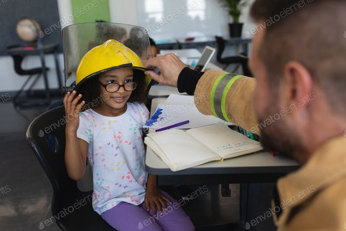 Firefighter wearing helmet to a schoolgirl in classroom