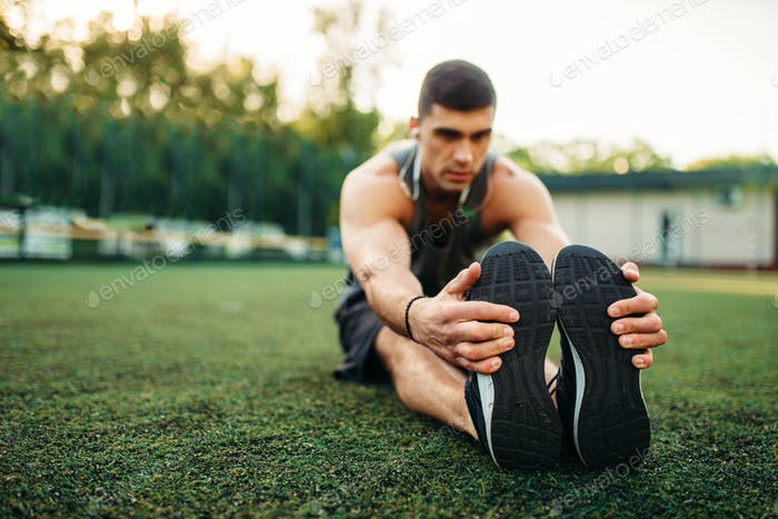 Man in sportswear heats up before outdoor training