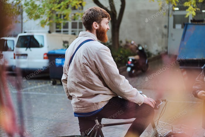 Back view of young attractive man riding on bicycle through streets
