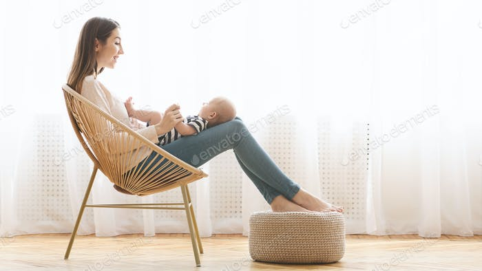 Mother relaxing in chair with her newborn baby on laps