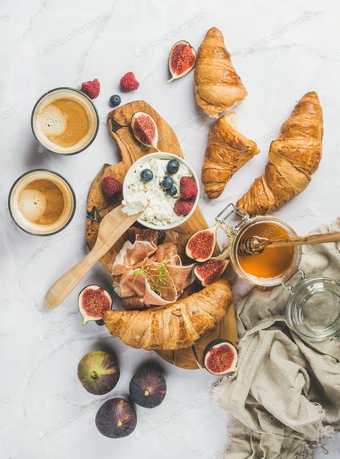 Frühstück mit Croissants, Ricotta, Kaffee und Beeren auf Marmor Hintergrund