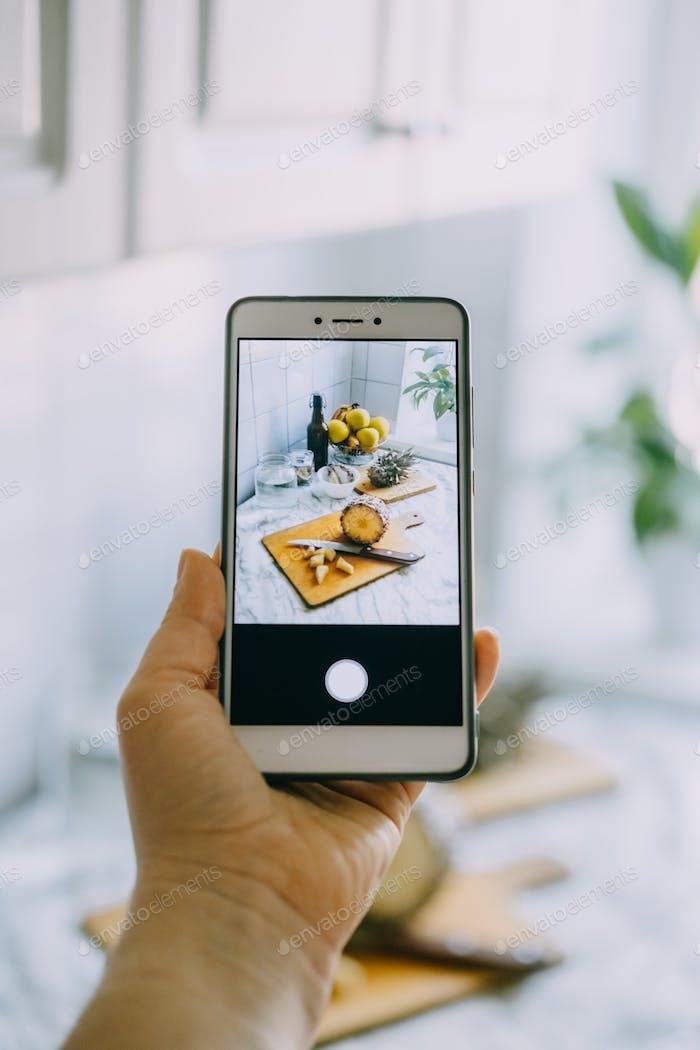 Food-Blogger macht Foto auf Smartphone für soziale Netzwerke. Weibliche Hand hält Handy mit