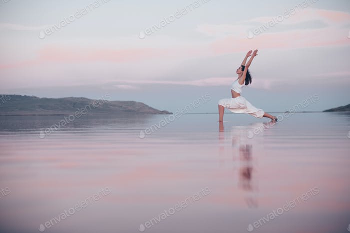 Young woman doing yoga at the lake