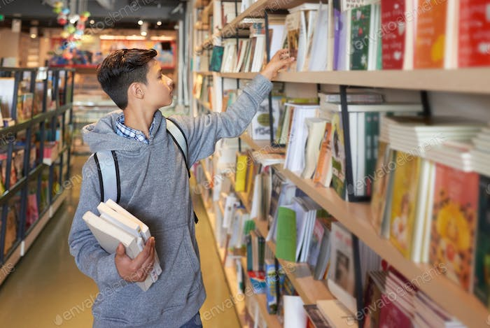 Student in library choosing books