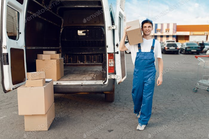 Deliveryman poses at the car with parcel boxes