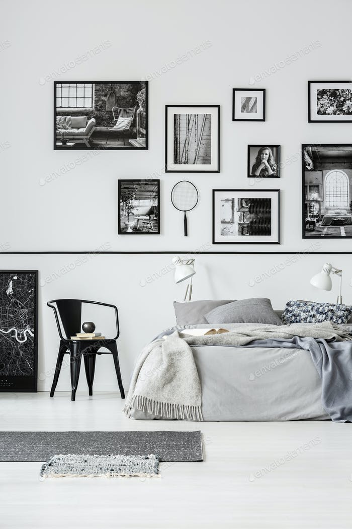 Rugs and black chair next to bed in white bedroom interior with photo by  bialasiewicz on Envato Elements