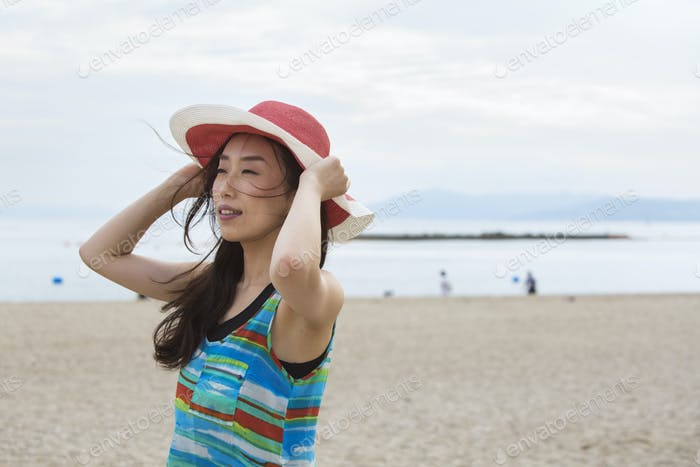 A woman on a beach in Kobe holding her hat on.