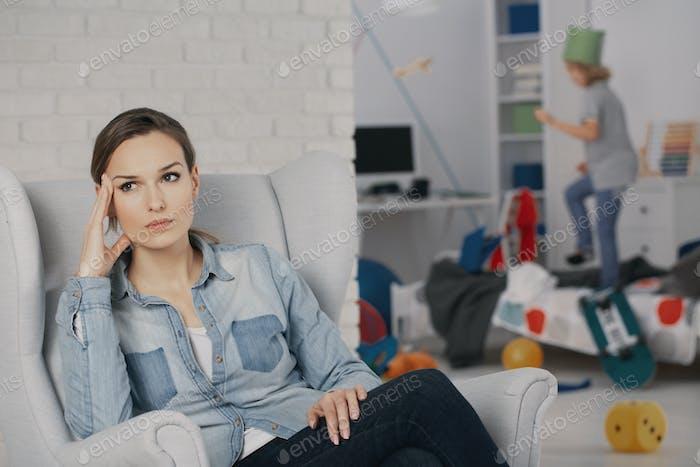 Sorgen Mutter entspannt auf Sessel, während Sohn mit adhd macht ein