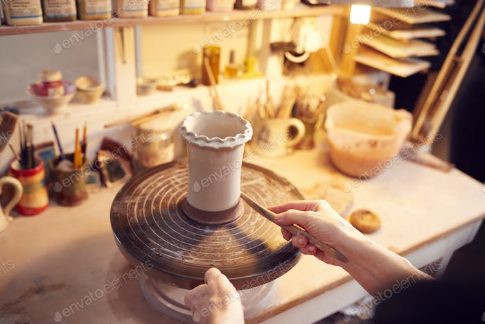 Close Up Of Potter Applying Glaze To Clay Vase In Ceramics Studio