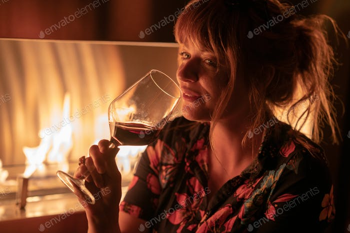 Beautiful ginger girl drinking a glass of vodka near a fire pit