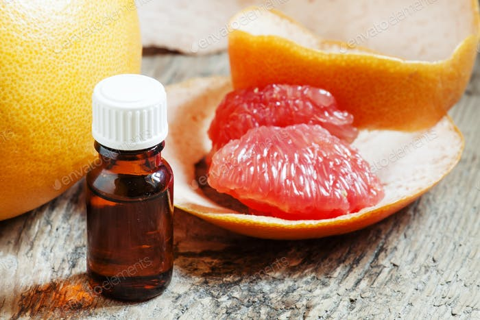 Grapefruit essential oil in a small bottle and fresh grapefruit