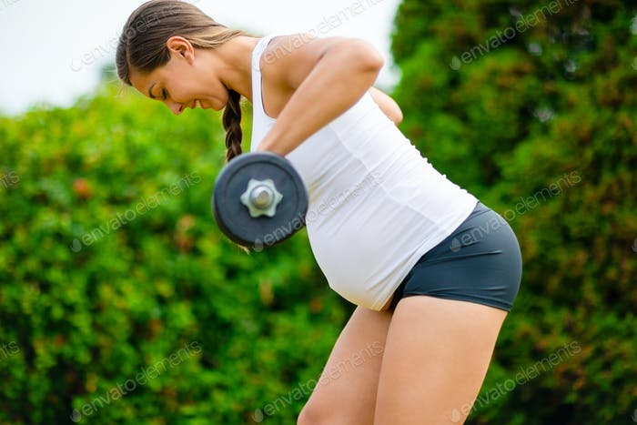 Young Pregnant Woman Doing Back Workout With Dumbbells In Park