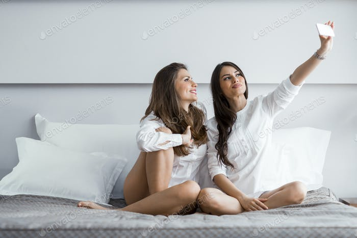 Two hot girls lying on a bed taking a photo of themselves with