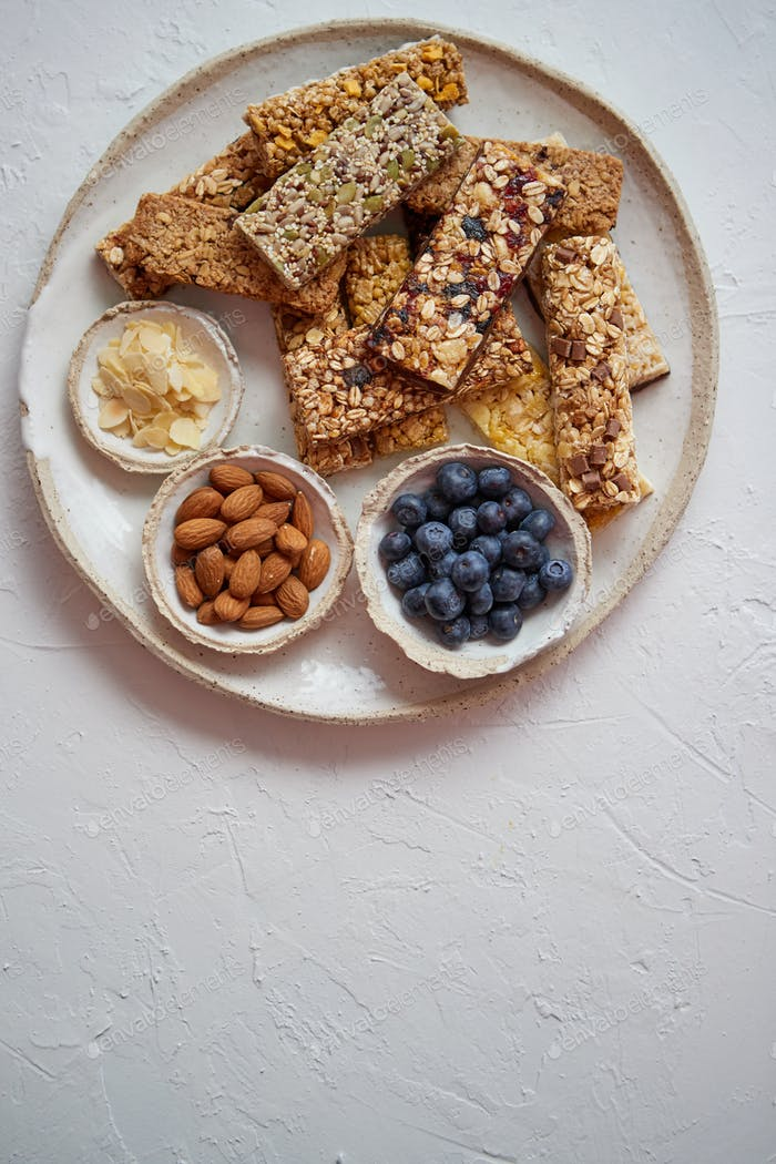 Thumbnail for Mixed composition of energy nutrition bar, granola on ceramic plate over white background