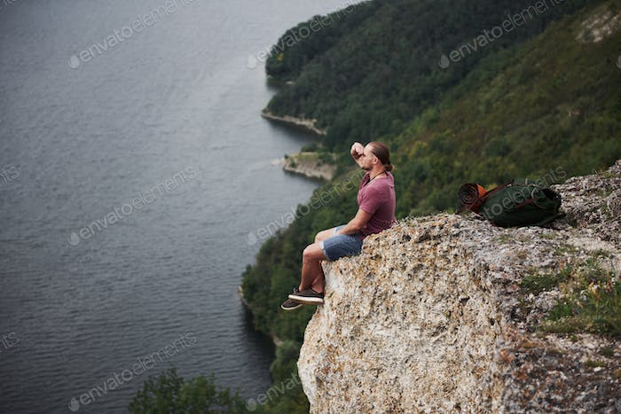 Traveller with backpack sitting on top of mountain enjoying view above the water surface. Traveling