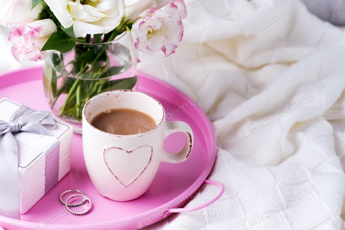 A tray with a cup of coffee, gift box, flowers and rings on the bed. Valentine's Day Wedding