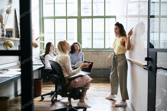 Frau zeigt auf Whiteboard in einem Treffen mit weiblichen Team